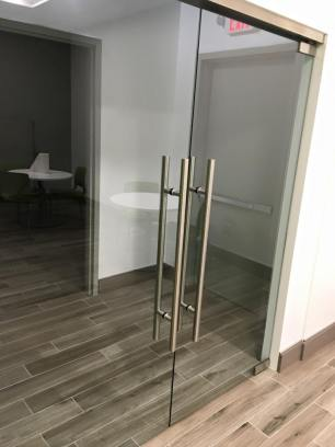 "Pair of 1/2"" clear glass entry doors for an office."