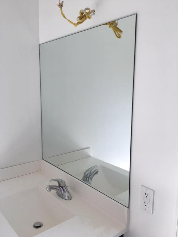 Wall-mounted vanity mirror.
