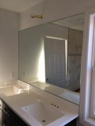 Wall-mounted vanity mirror.