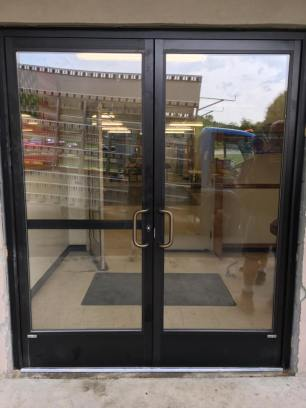 Commercial entry doors with tempered insulated glass and a rim panic bar on active leaf.