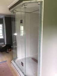 Frameless shower enclosure with four individual panels & a door in the center.