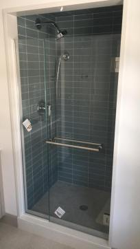"Door with side-mount hinges and a fixed panel held in place with polished chrome channel (glass: 1/2"" Starphire®️ glass with Showerguard®️ coating)"
