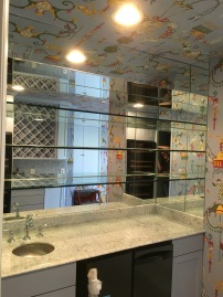 """Custom-designed bar area - three 1/2"""" tempered glass shelves secured into the wall with chrome channel, with individual pieces of mirror cut to fit in between."""