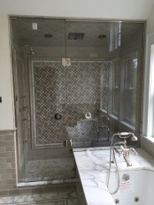"""Custom steam shower configuration based on architect's design, with a notched panel held in place with channel and clamps, and door mounted on the panel with glass-to-glass hinges (1/2"""" low-iron/ """"ultrawhite"""" glass with Showerguard coating)."""