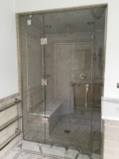 """Steam shower panel-door-panel enclosure - side panels secured with polished chrome channel and glass clamps, with a door mounted on the panel (1/2"""" low-iron/ """"ultrawhite"""" glass with Showerguard coating)."""