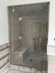 "Steam shower panel-door-panel enclosure - side panels secured with polished chrome channel and glass clamps, with a door mounted on the panel (1/2"" low-iron/ ""ultrawhite"" glass with Showerguard coating)."