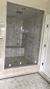 "Steam shower enclosure - door with top and bottom pivots flanked by panels secured with polished chrome channel (1/2"" low-iron / ""ultrawhite"" glass with Showerguard)."
