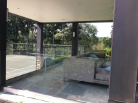 Tempered laminated glass installed around a client's outdoor living area, to provide an unobstructed view of their tennis court.