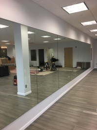 """1/4"""" mirrors with polished edges installed along the wall of a dance studio, using """"J"""" channel on the top and bottom."""