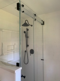 """Phantom"" sliding bypass shower door system, with a return on a buttress."
