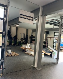 """1/4"""" mirrors with polished edges, installed in the weightlifting area of a gym."""